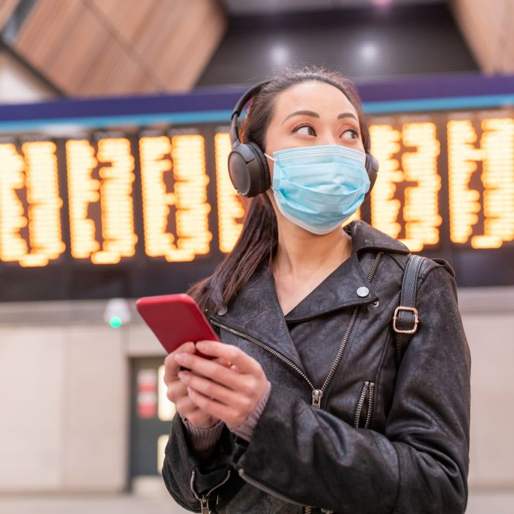 Woman with face mask at the airport checking her smartphone